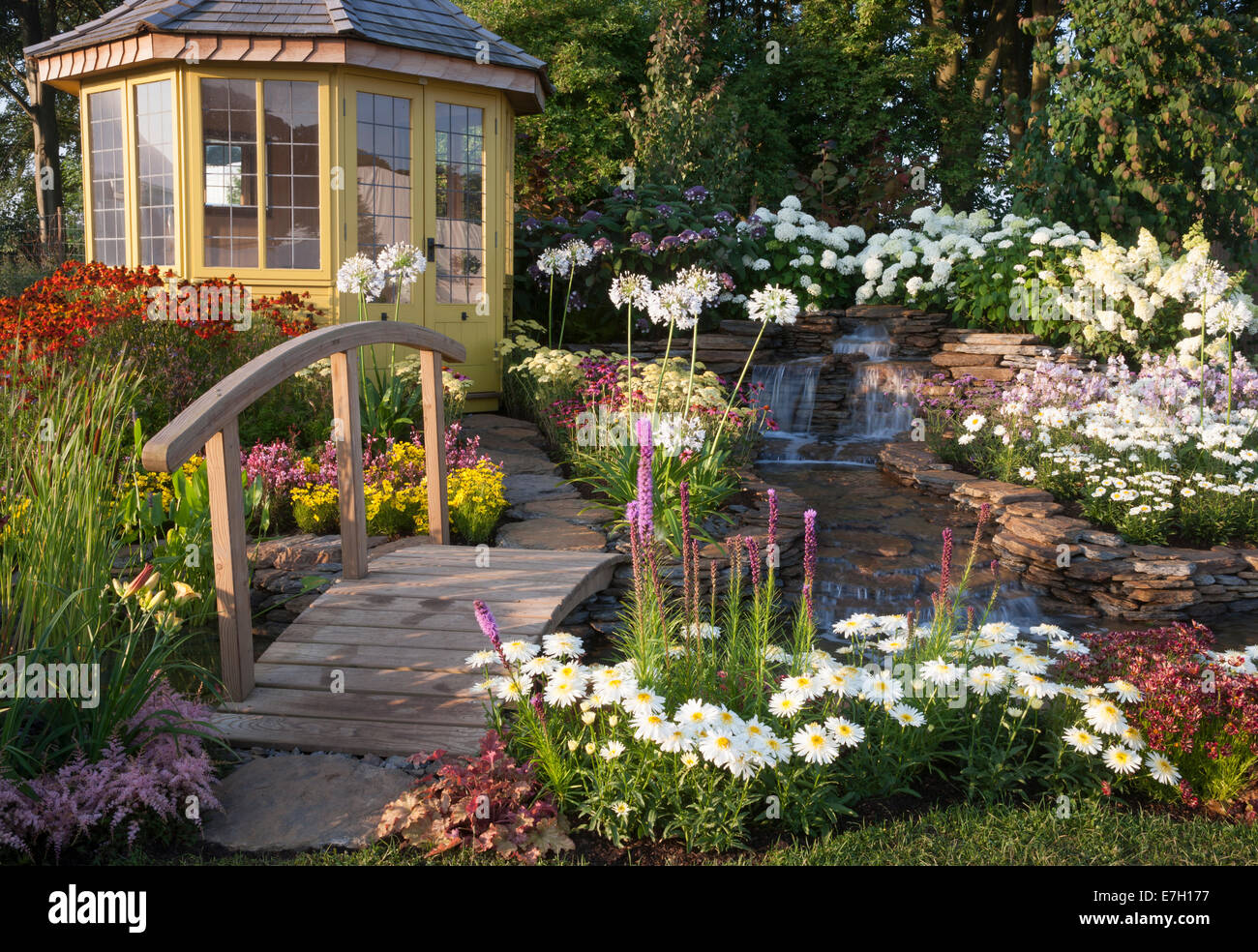 Garden - The Water Garden - summerhouse next to waterfall water feature with small wooden bridge and planting - Stock Image
