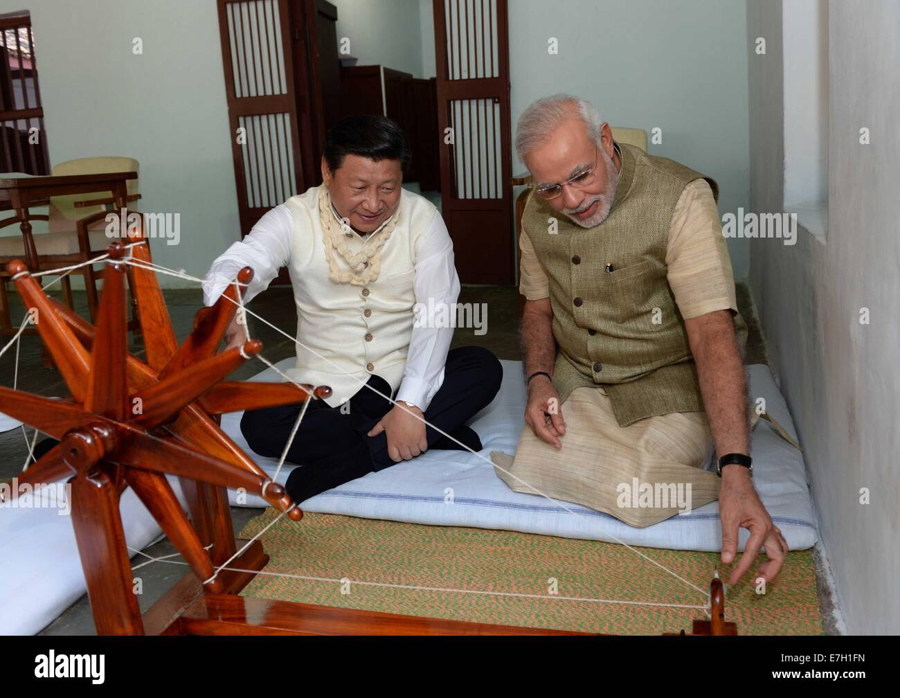 New Dehli, India. 17th Sep, 2014. Chinese President Xi Jinping (L) rotates a spinning wheel that was once used by Stock Photo