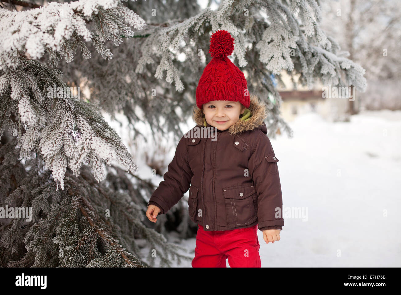 Portrait of child in brown jacket and red knitted hat and red trousers, lots of snow. Winter forest - Stock Image