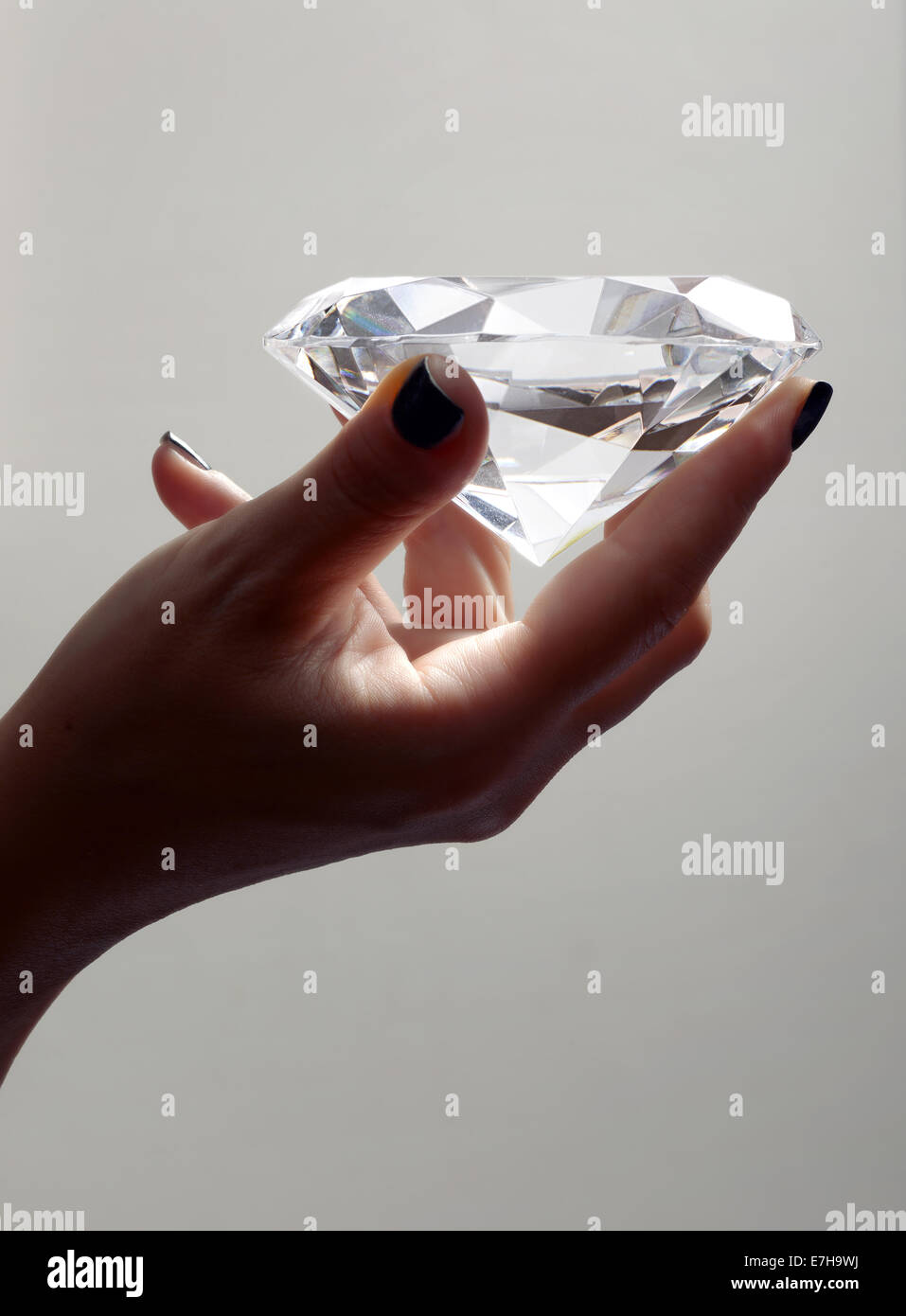 Female Hand Holding Over sized Illuminated Diamond in Studio with Grey Background - Stock Image