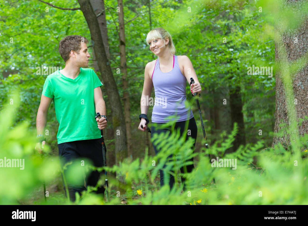 Young sporty active couple with hiking sticks walking in nature. Active lifestyle. Activities and recreation outdoors. - Stock Image