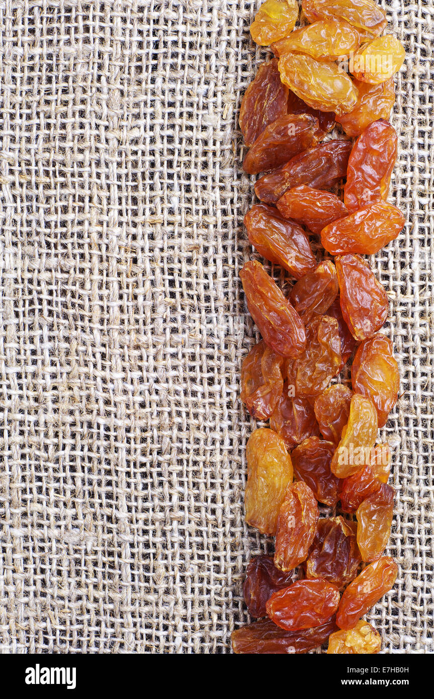Raisins on burlap background closeup - Stock Image