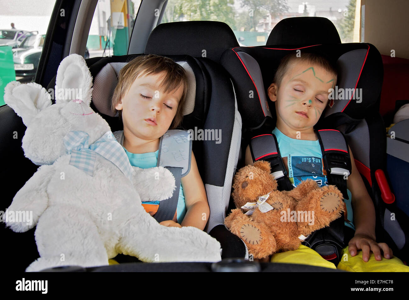 Two boys in car seats, traveling, sleeping in the car with teddy bears - Stock Image