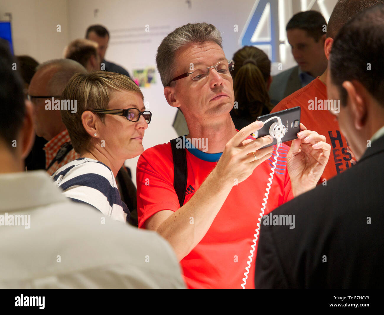 Couple looking at the latest Samsung smartphone at the 2014