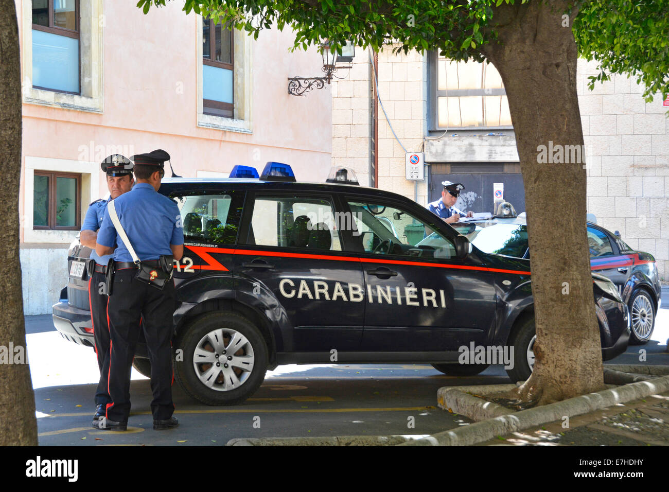 Carabinieri officers beside parked cars outside police station in Taormina Province of Messina Sicily Italy - Stock Image