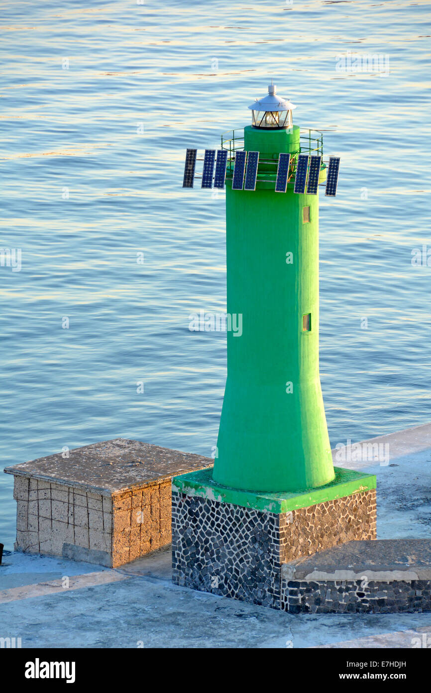 Solar panels fitted to green channel marker light on end of harbour wall at Port of Naples Campania Italy - Stock Image
