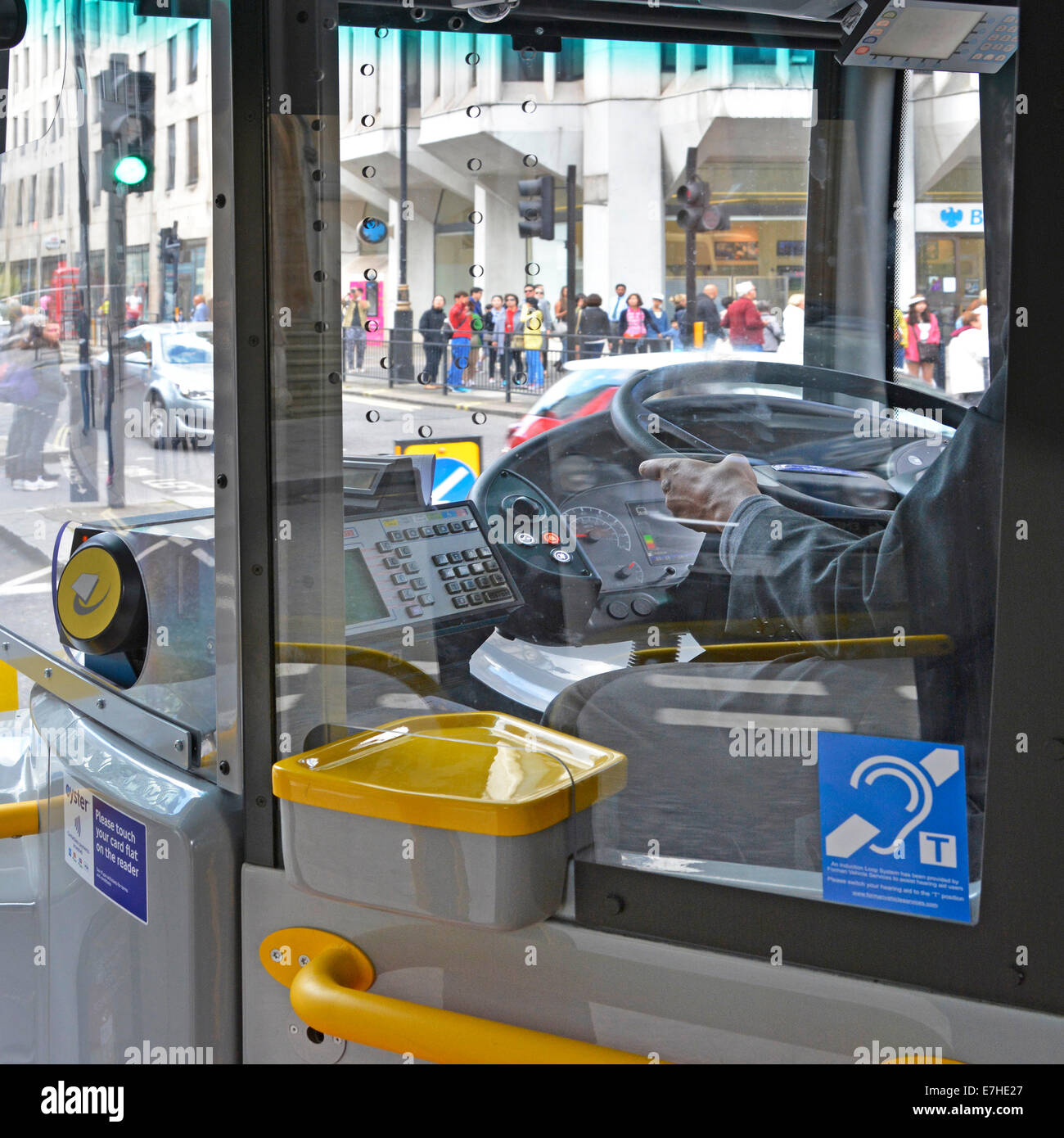 London bus driver at work right hand drive steering wheel interior cab with Oyster card reader and hearing pictogram - Stock Image