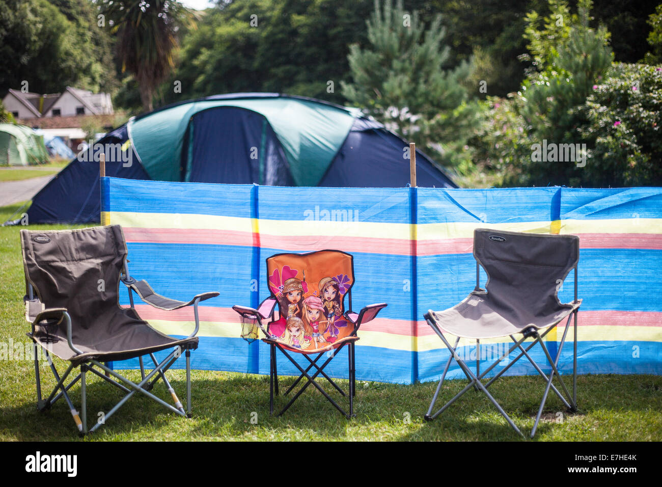 Glamping and camping chairs and windbreak on a campsite - Stock Image