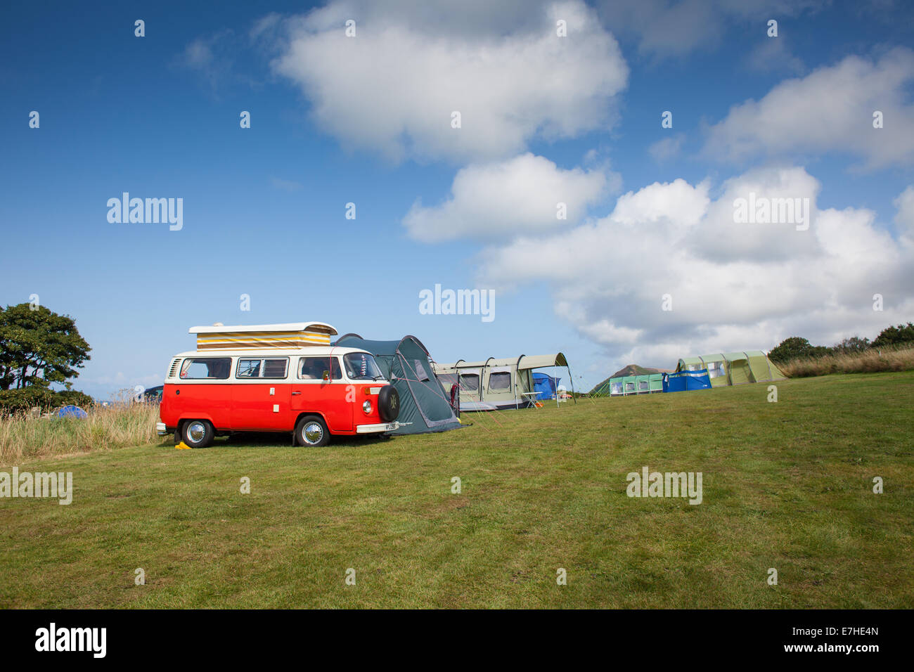 A red VW camper van on a campsite with tens and blue sky - Stock Image