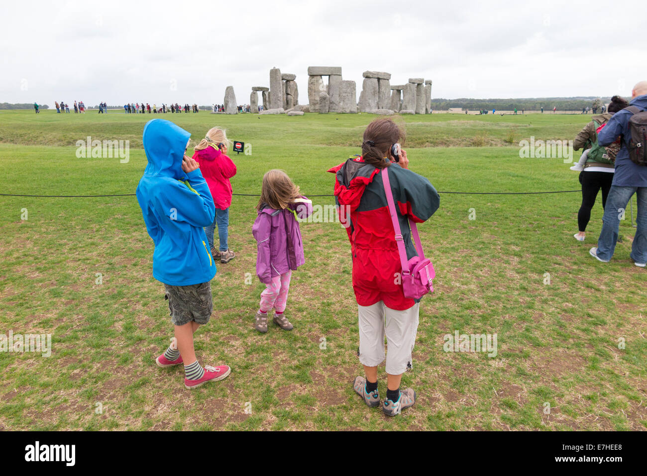 Visitors to Stonehenge: Stone Henge with tourists / tourist family / mum mother and children / kids listening to audio guide. UK Stock Photo