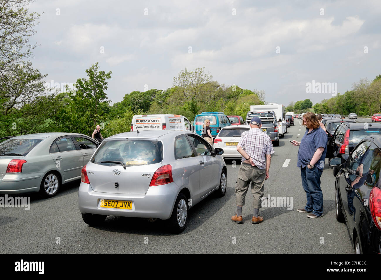 People standing on carriageway outside stationary vehicles in a traffic jam on M6 motorway due to accident causing - Stock Image