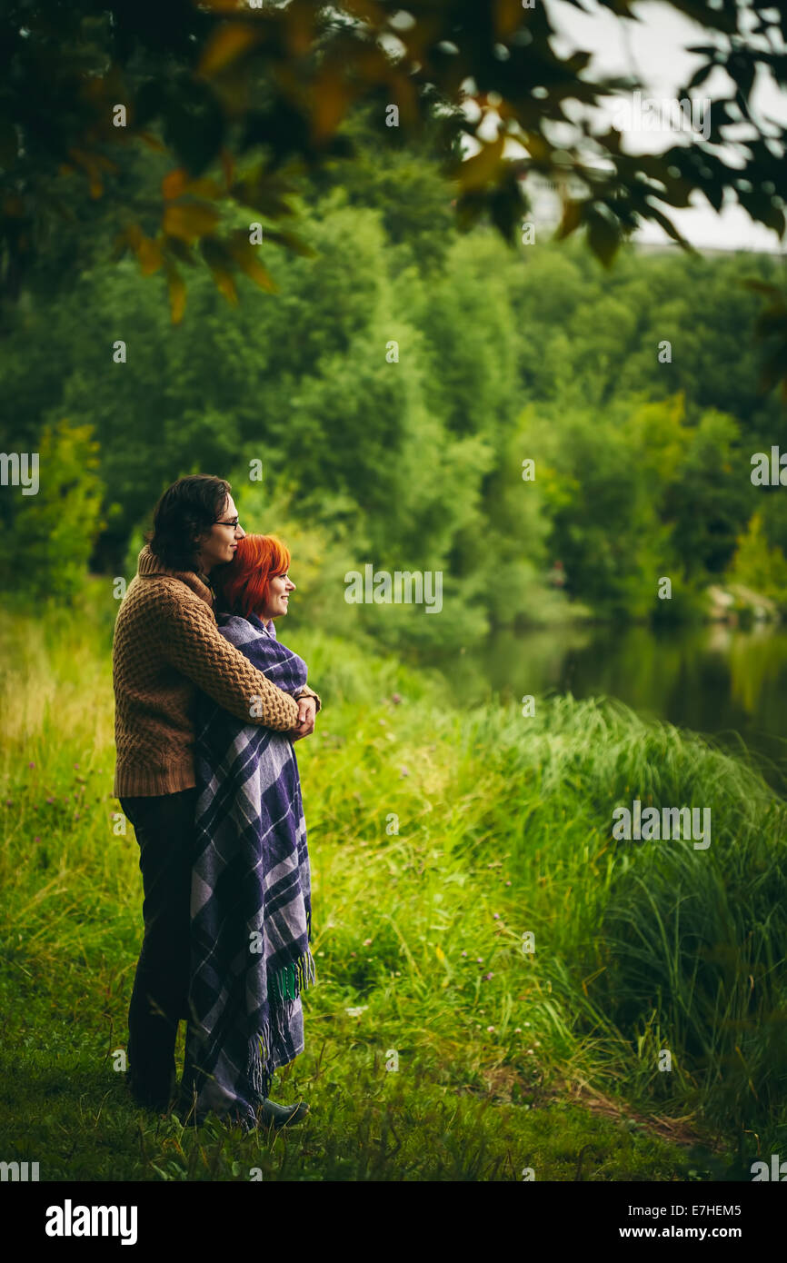 Young happy couple standing near water in green forest, looking ahead. Man holding woman. - Stock Image