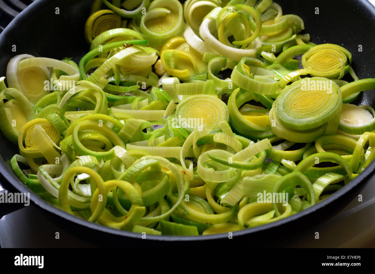 Closeup of fried leek vegetable in a pan during home cooking. - Stock Image