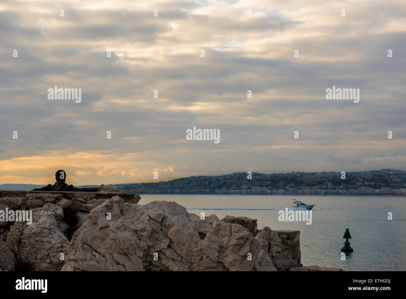 Solitary man watches the sunset over the Baie des Anges in Nice, France Stock Photo