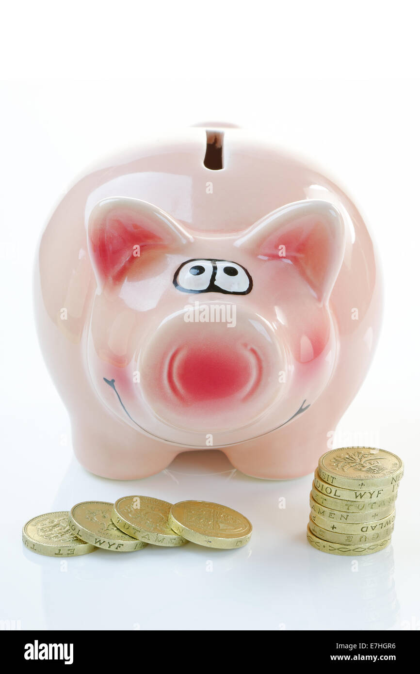 A pink piggy bank with coins. Savings and investment concept - Stock Image