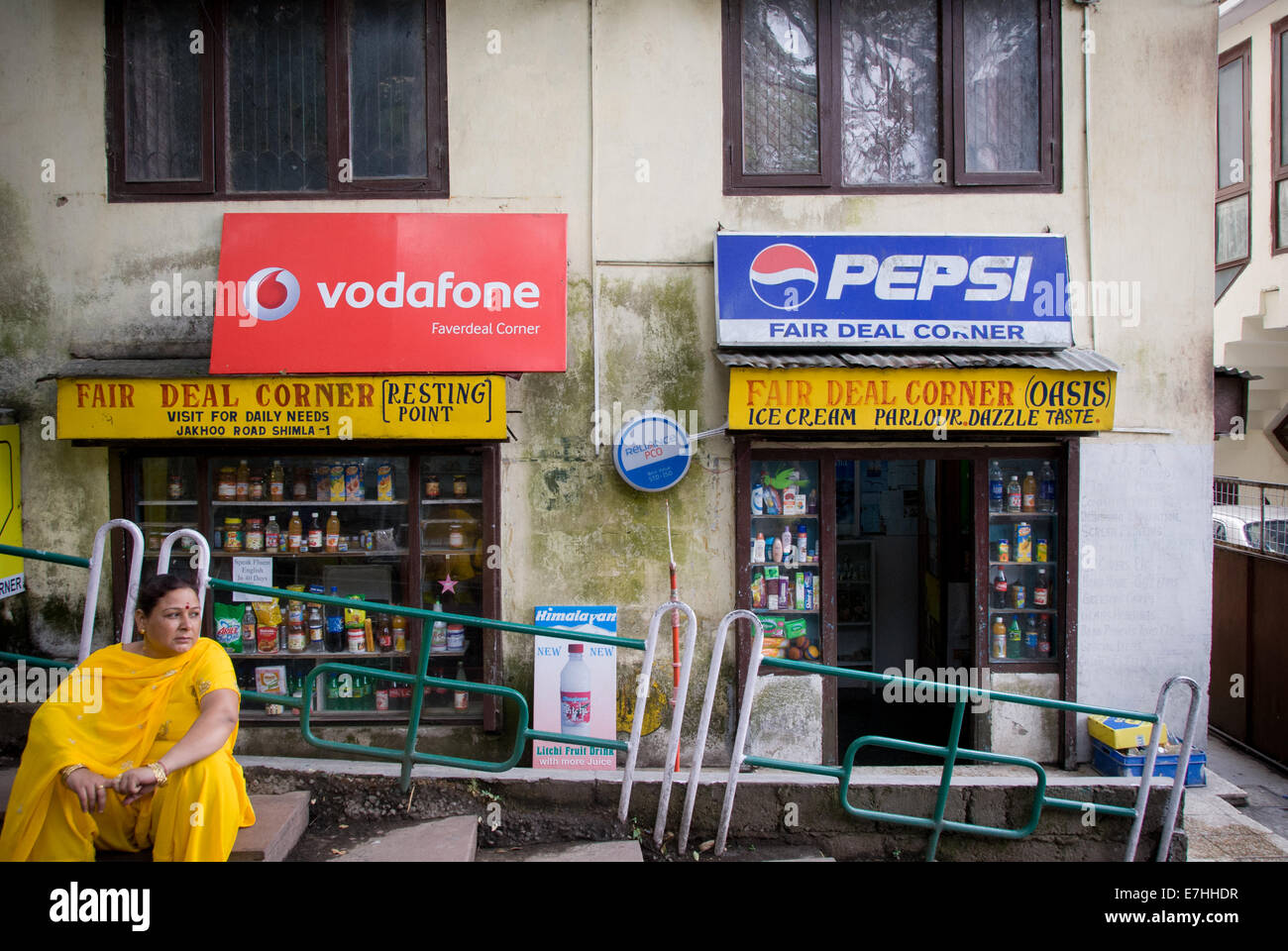 Indian woman in sari in front of billboards for Western companies in Shimla India - Stock Image
