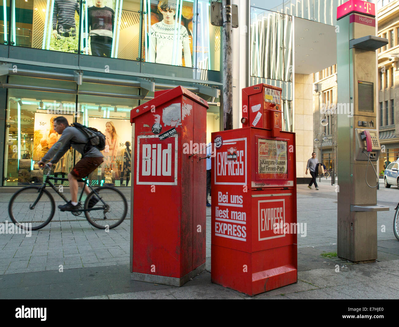 Newspaper vending machines in the street in Cologne, Germany with T-Mobile hotspot pole and cyclist - Stock Image