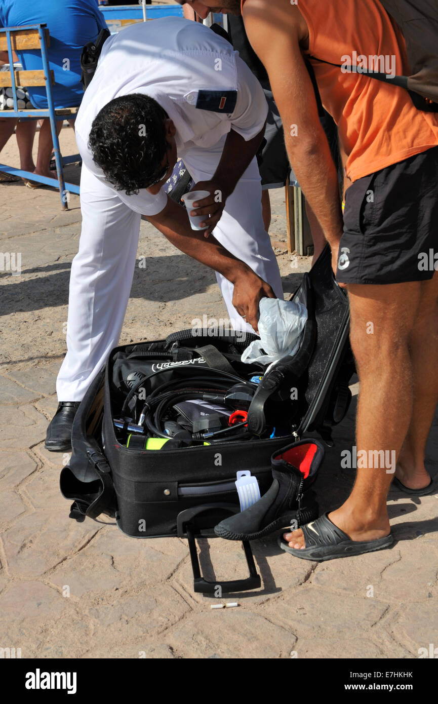 Scuba diver having luggage security checked before boarding boat at 'Sharks Bay' in Sharm El Sheikh by the - Stock Image
