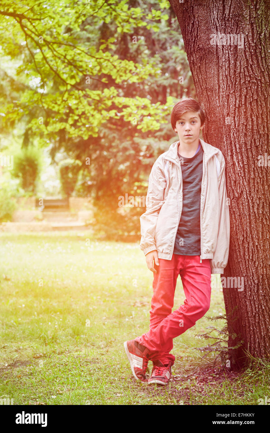 teenager boy leaning against a tree in a park. - Stock Image