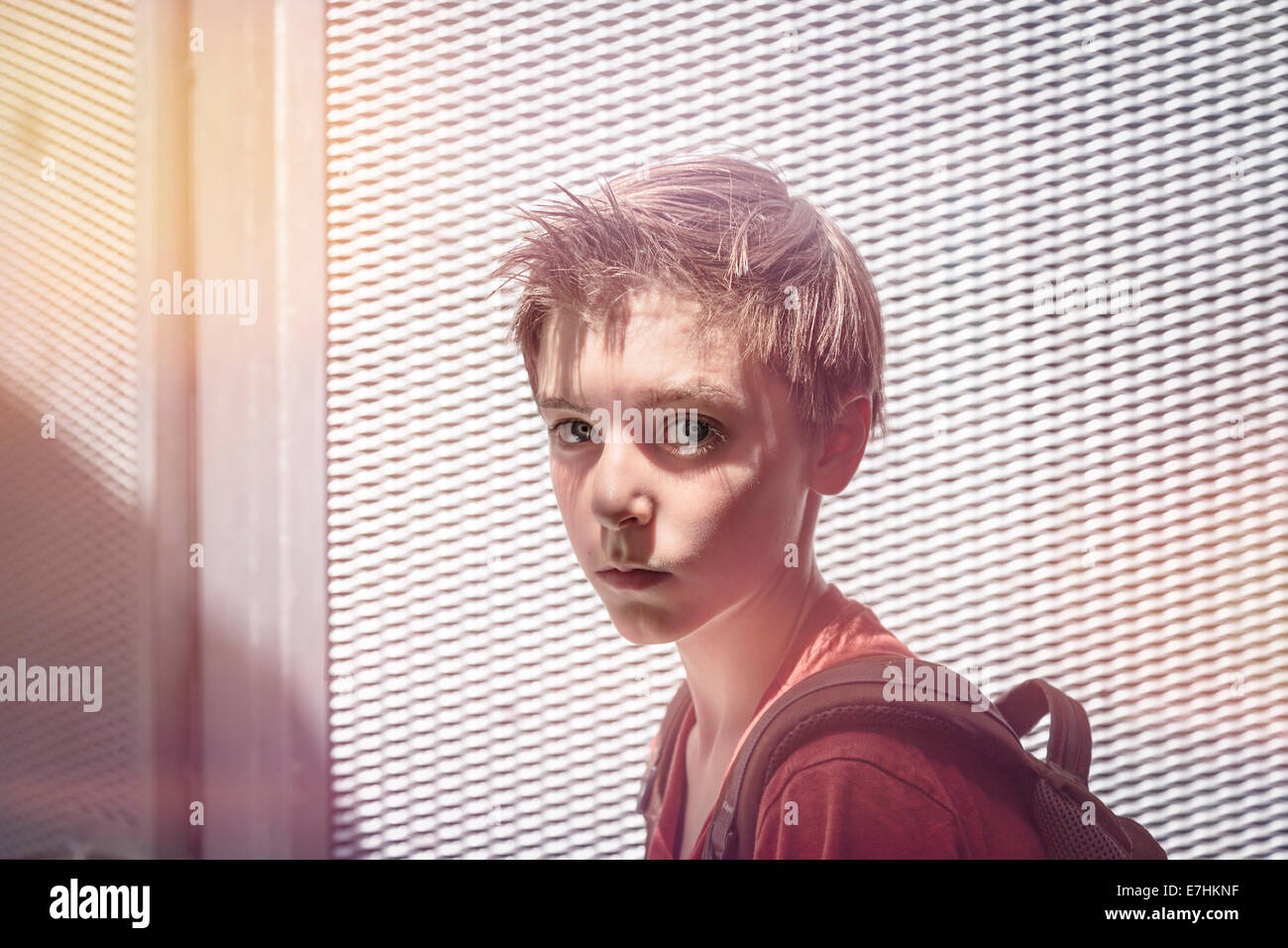 portrait of a teenager boy with rucksack and extreme light in front of a metal grid pattern - Stock Image