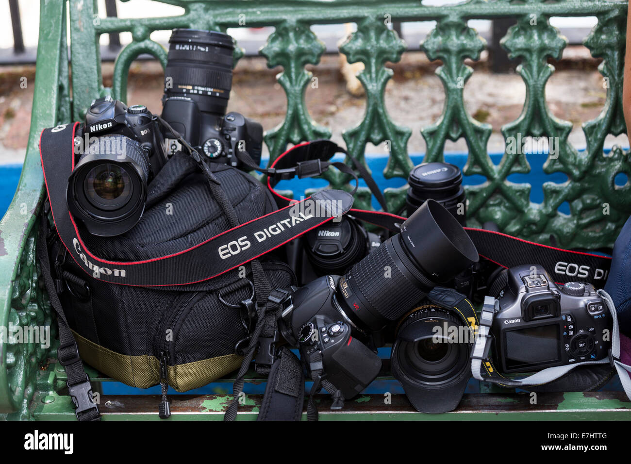 Group of SLR cameras on a green bench - Stock Image