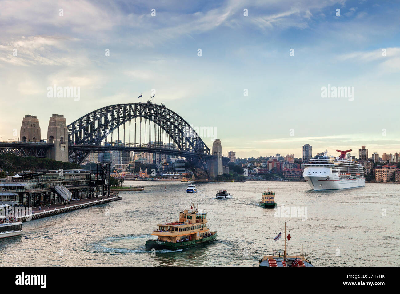 Twilight in busy Sydney Harbour, as the cruise liner Carnival Spirit leaves its berth at Circular Quay. Stock Photo