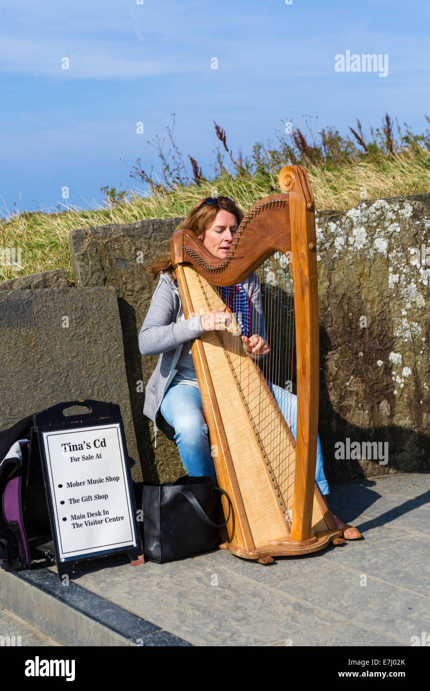 Harpist playing at the Cliffs of Moher, The Burren, County Clare, Republic of Ireland - Stock Image