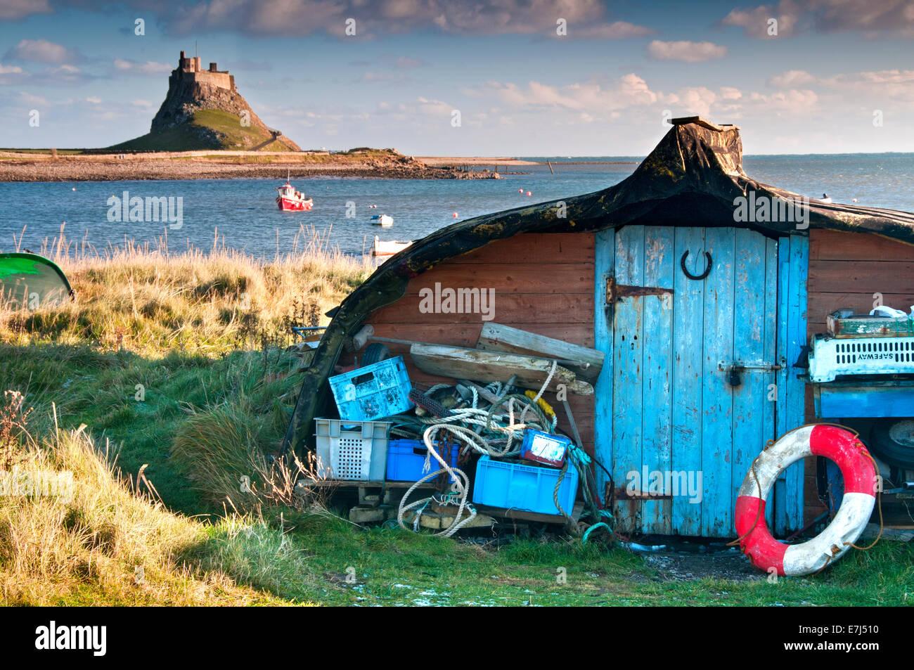 Upturned Boat Hull Sheds and Lindisfarne Castle, Holy Island, Northumberland, England, UK - Stock Image