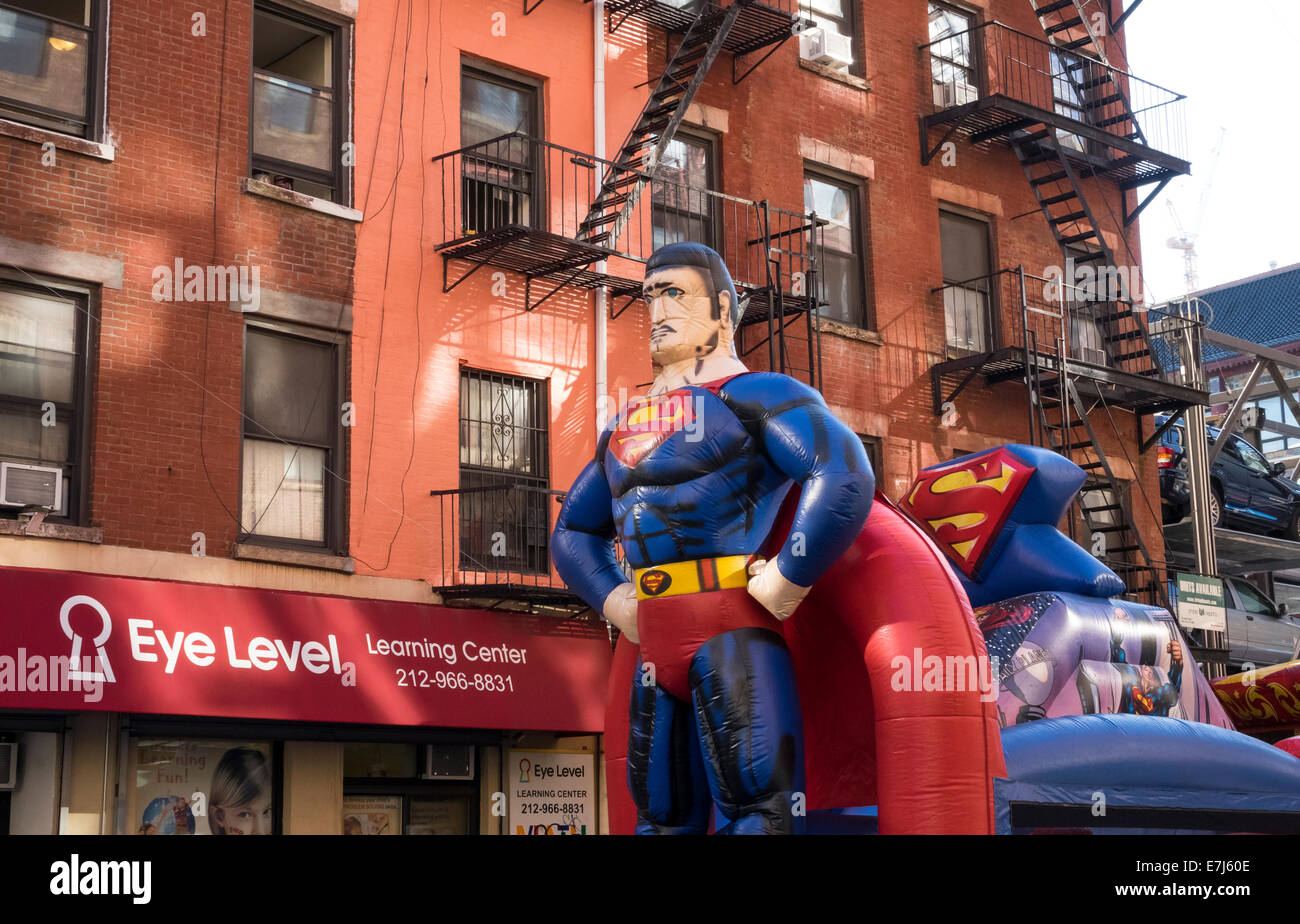 Giant Superman blowup doll on a children's amusement ride in Little Italy in New York City - Stock Image