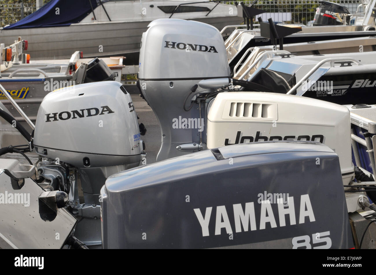 Various outboard engines on transoms of recreational vessels in boat yard ready for sale Stock Photo