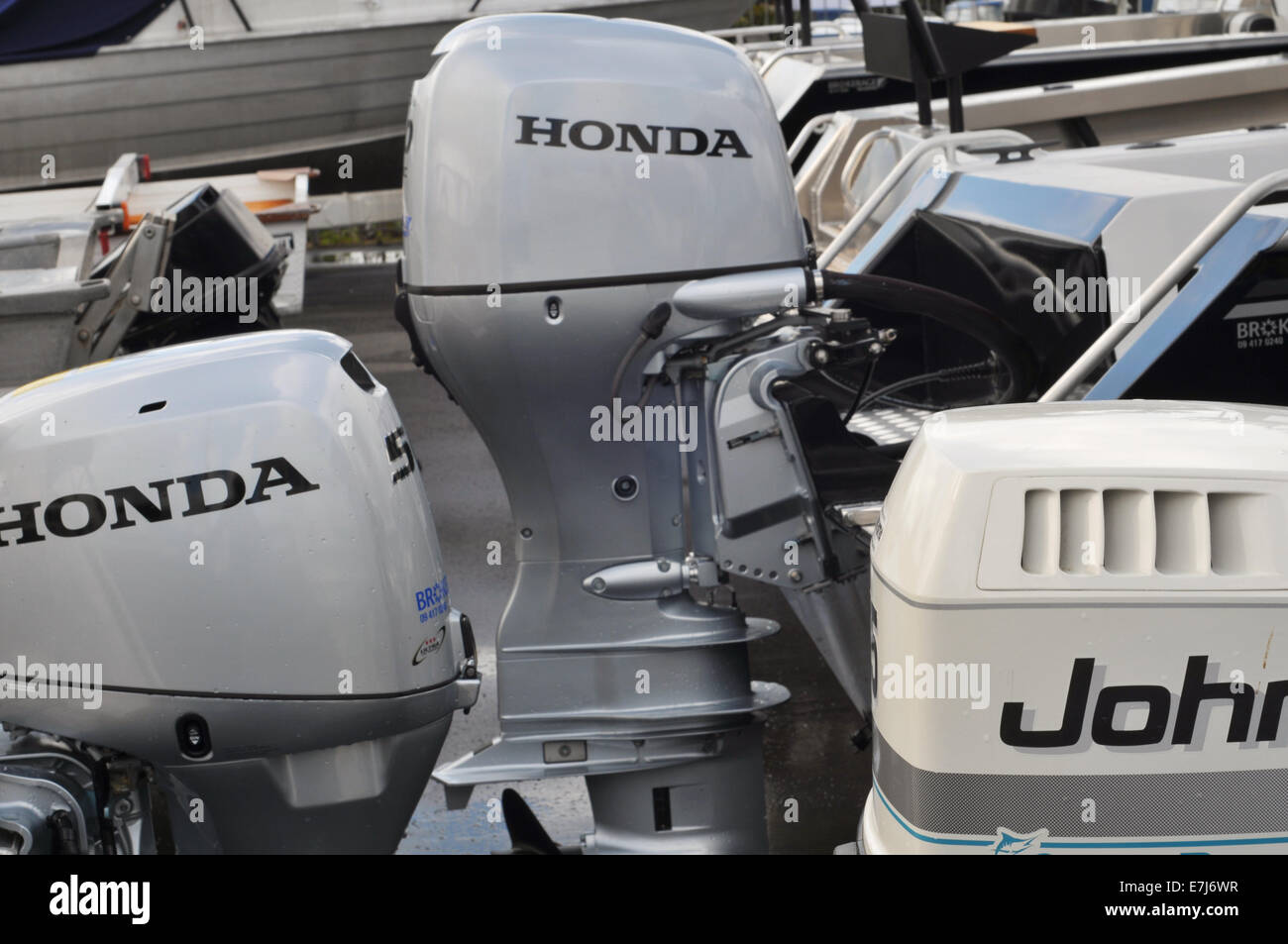 Various outboard engines on transoms of recreational vessels in boat yard ready for sale - Stock Image
