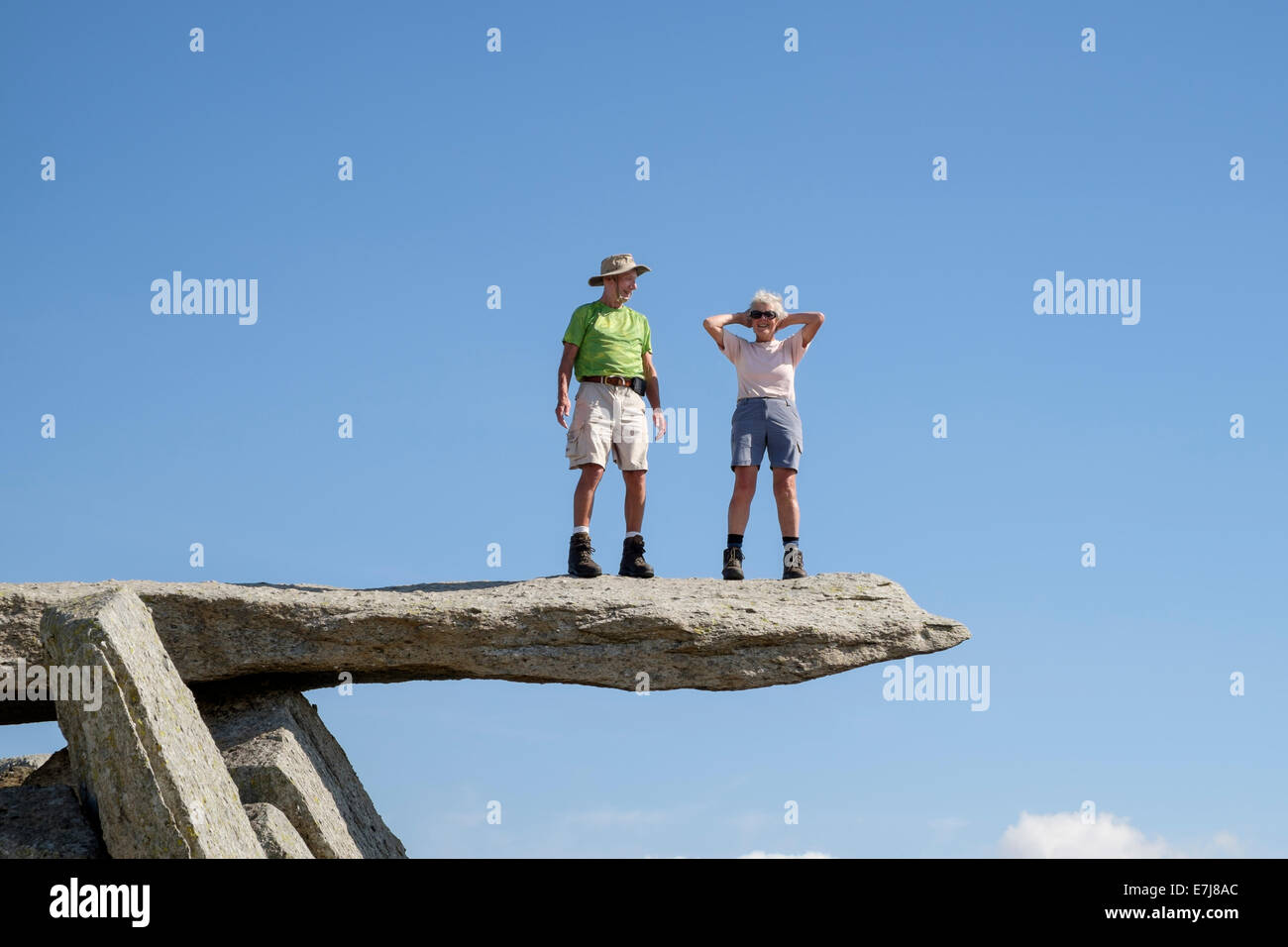 Two senior walkers standing on the cantilever rock on Glyder Fach in Snowdonia National Park, Wales, UK, Britain - Stock Image