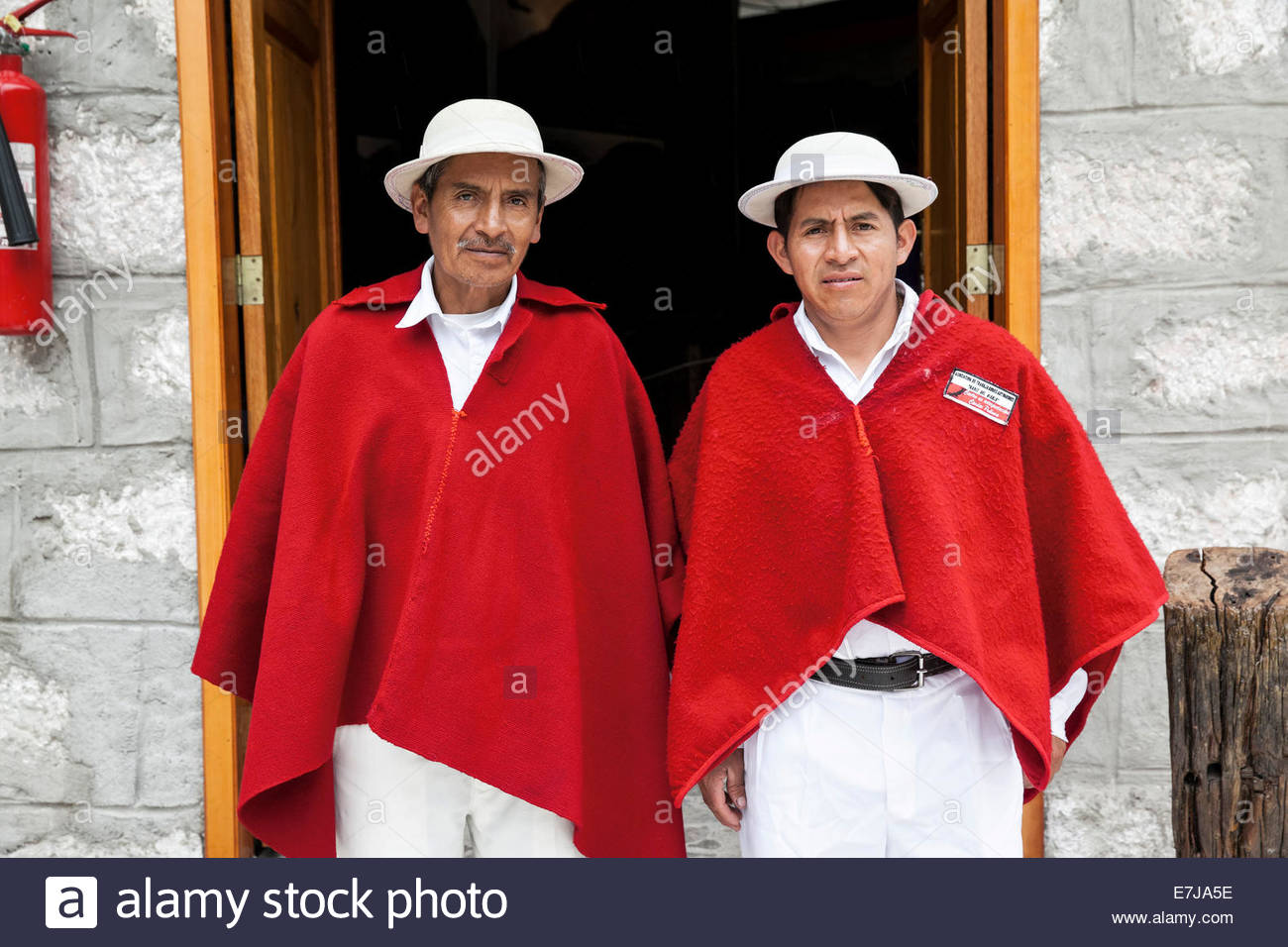 Men wearing red ponchos, Ecuador Stock Photo