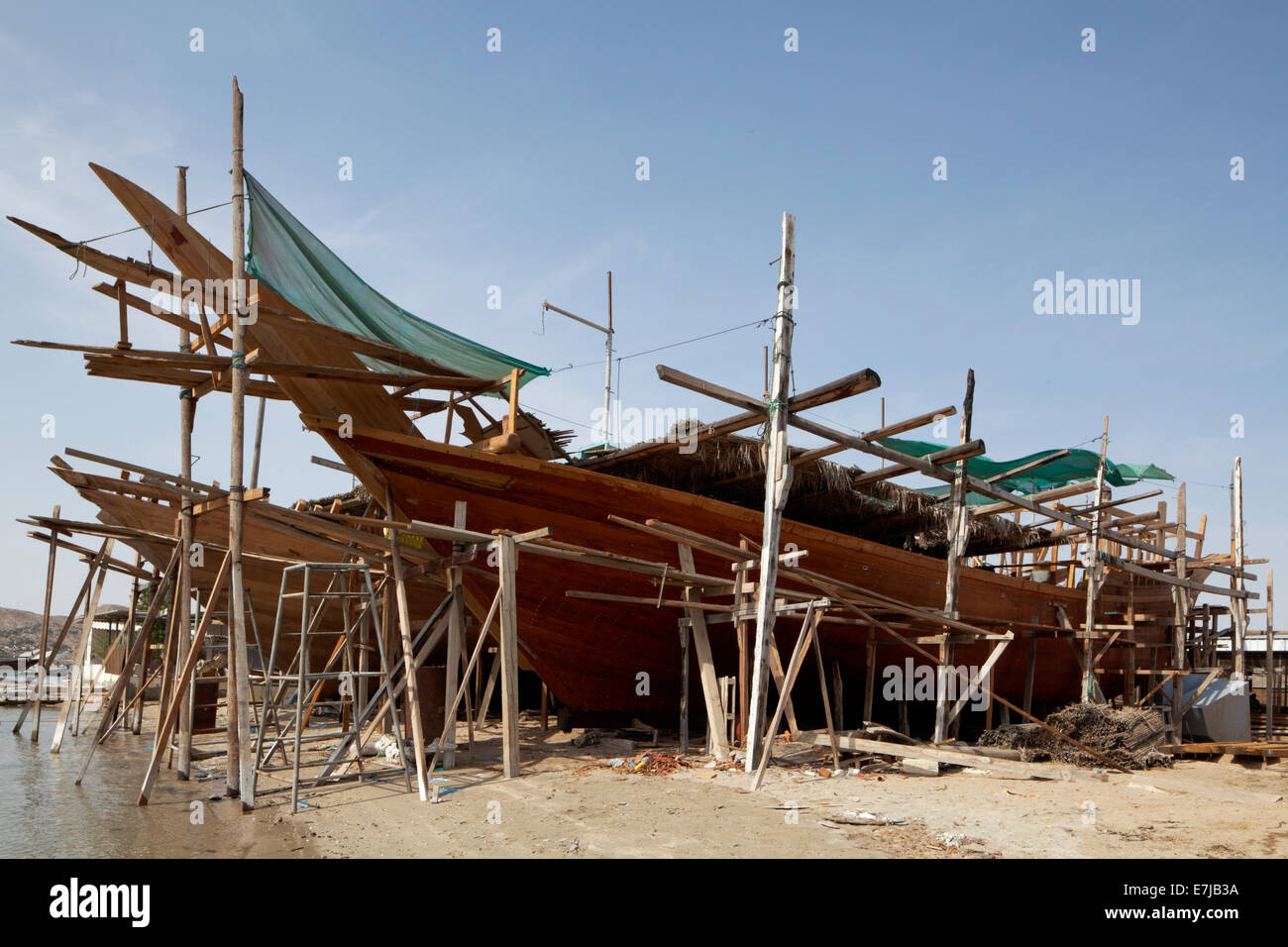Shipyard with an old dhow-ship being repaired, Sur, Ash Sharqiyah province, Sultanate of Oman, Arabian Peninsula - Stock Image