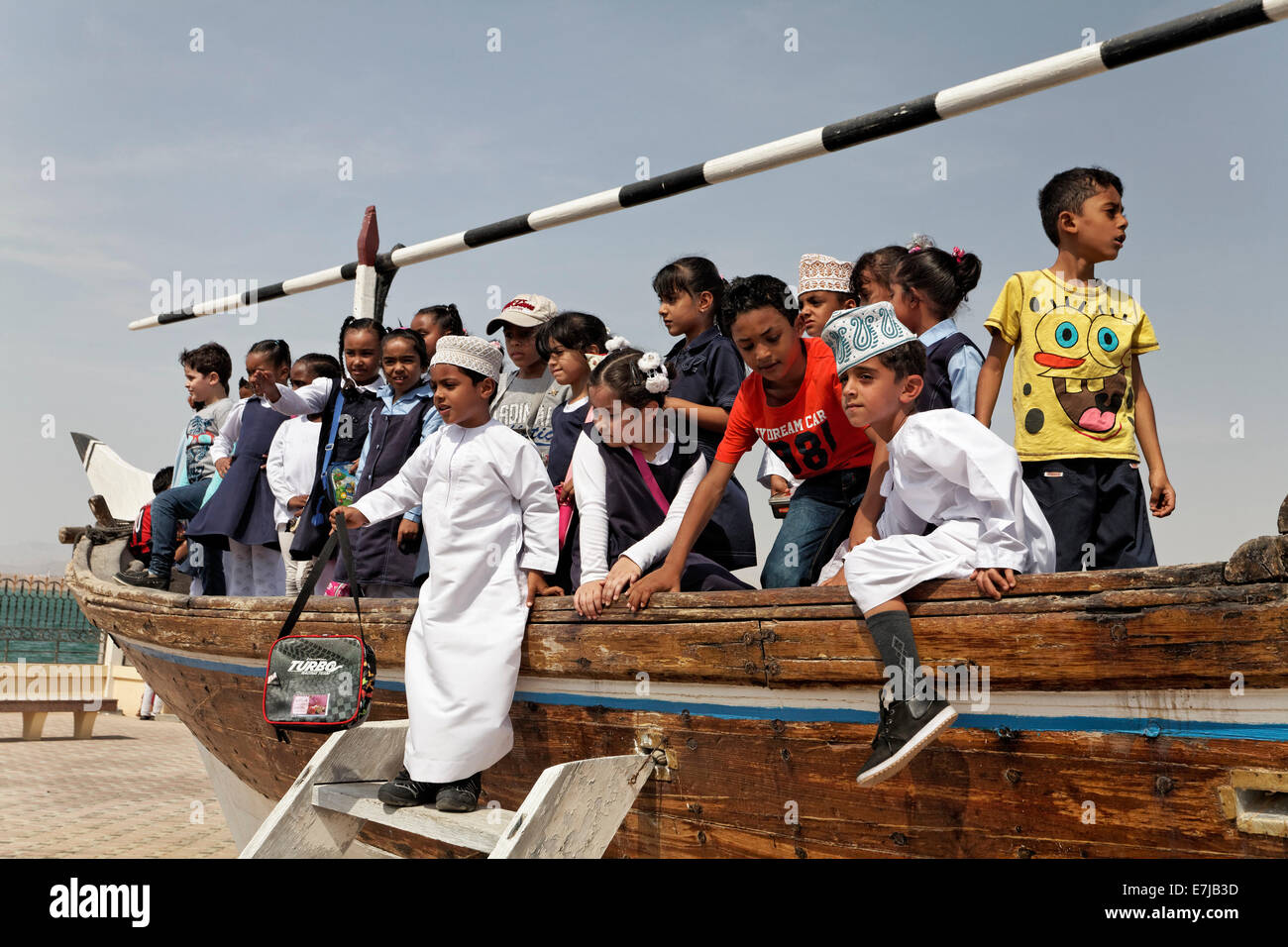 Group of Omani school children playing on an old dhow-ship, Dhow Museum, Sur, Ash Sharqiyah province, Sultanate - Stock Image