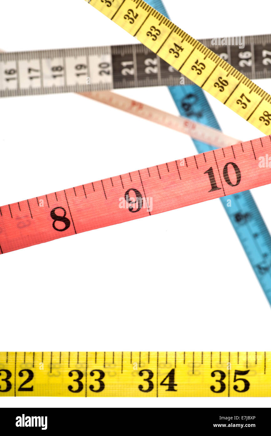 Various colourful tape measures criss-crossing over each other - Stock Image