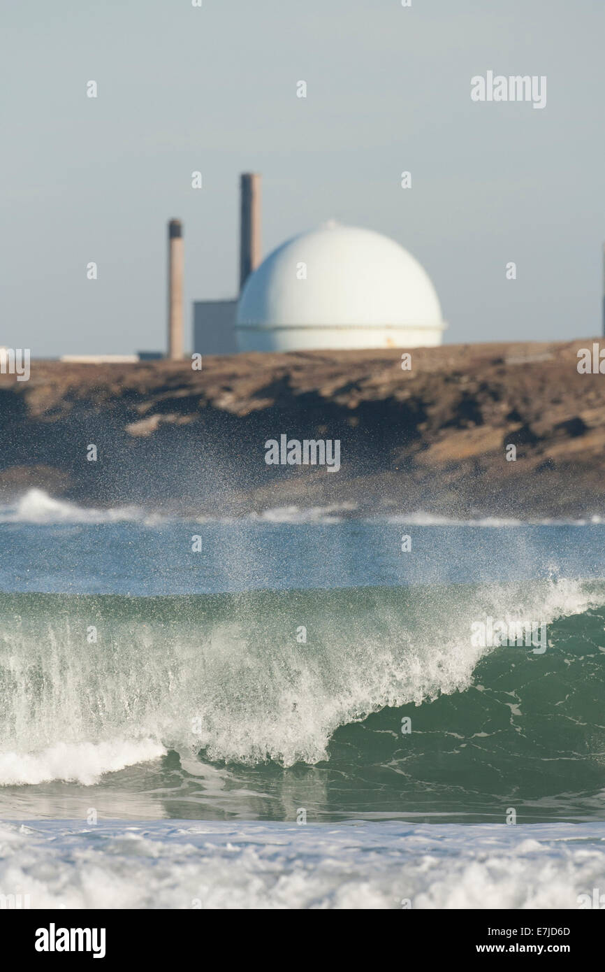 Wave crashing ashore with Dounreay Nuclear facility behind, Scotland Stock Photo