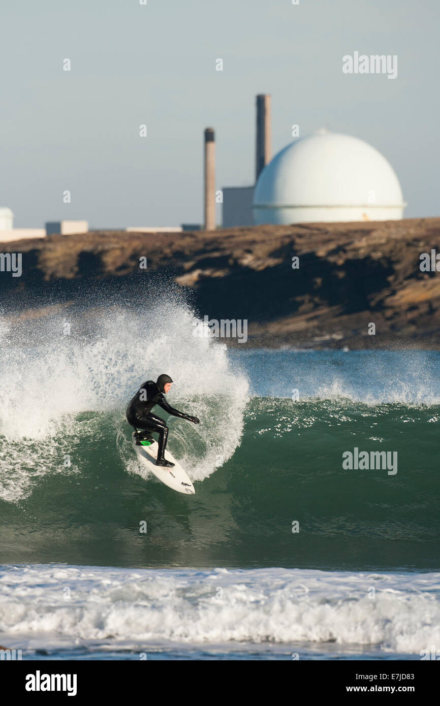 Surfer on big waves with Dounreay nuclear facility behind, Caithness Scotland - Stock Image