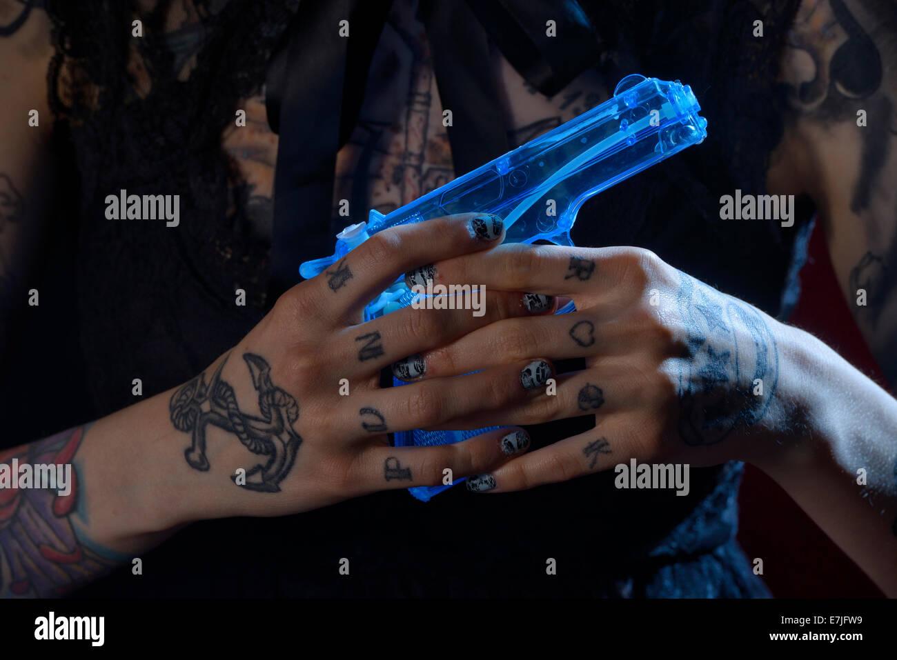 Hands, punk, squirt gun, water pistol, tattoo, hand, girl, dark, fingers, gun, USA - Stock Image