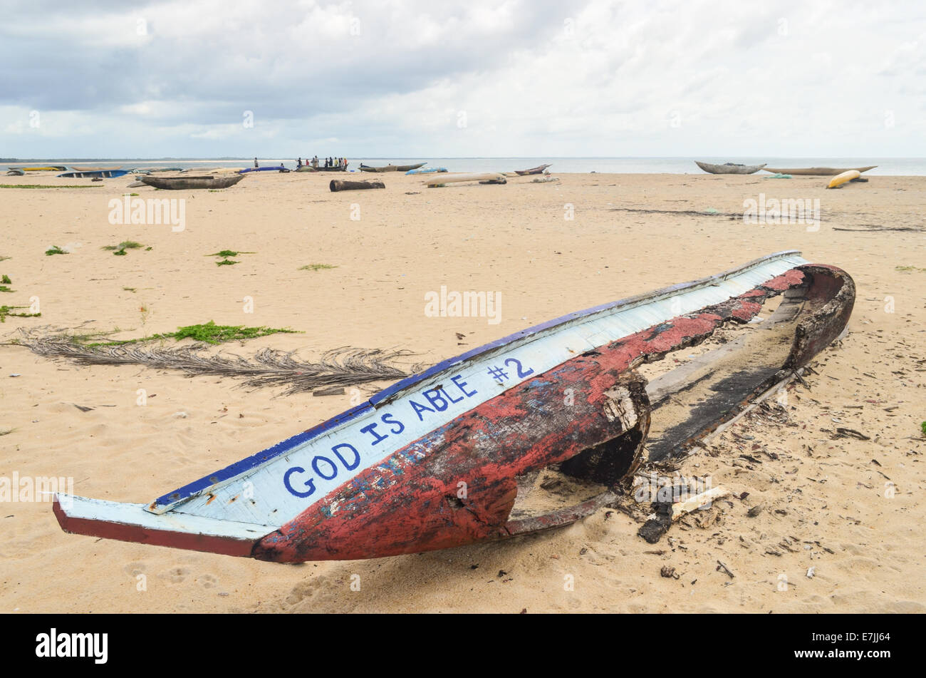 Wooden fishing boat wrecked on the beach of Robertsport, Liberia, reading 'God Is Able' - Stock Image