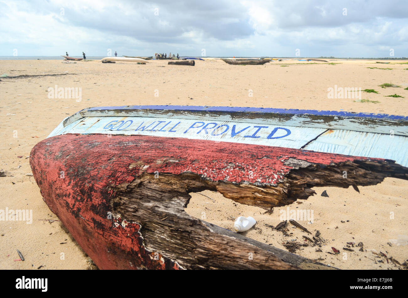 Wooden fishing boat wrecked on the beach of Robertsport, Liberia, reading 'God Will Provid' - Stock Image