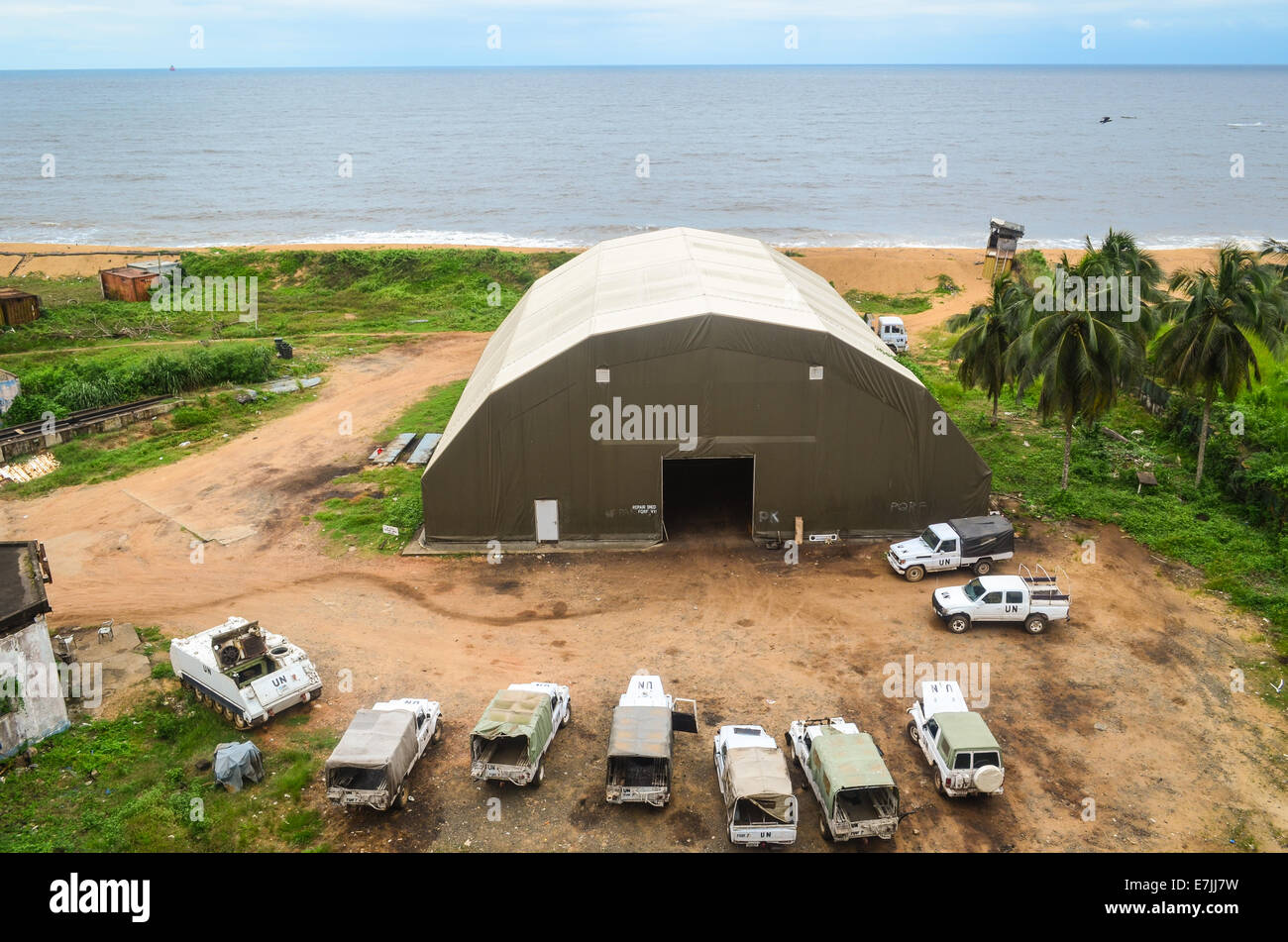 Vehicles and hangar of a UN camp in Monrovia, Liberia, seen from the top of the ruins of Hotel Africa - Stock Image