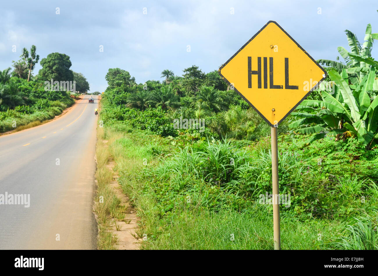 "Sign reading ""HILL"" in Liberia, Africa, ahead of a slope on a tar road near MonroviaStock Photo"