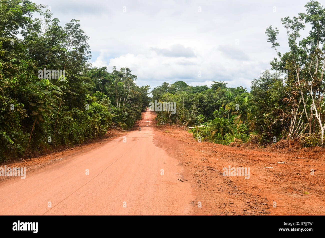 Red earth mud road in Liberia, Africa - Stock Image