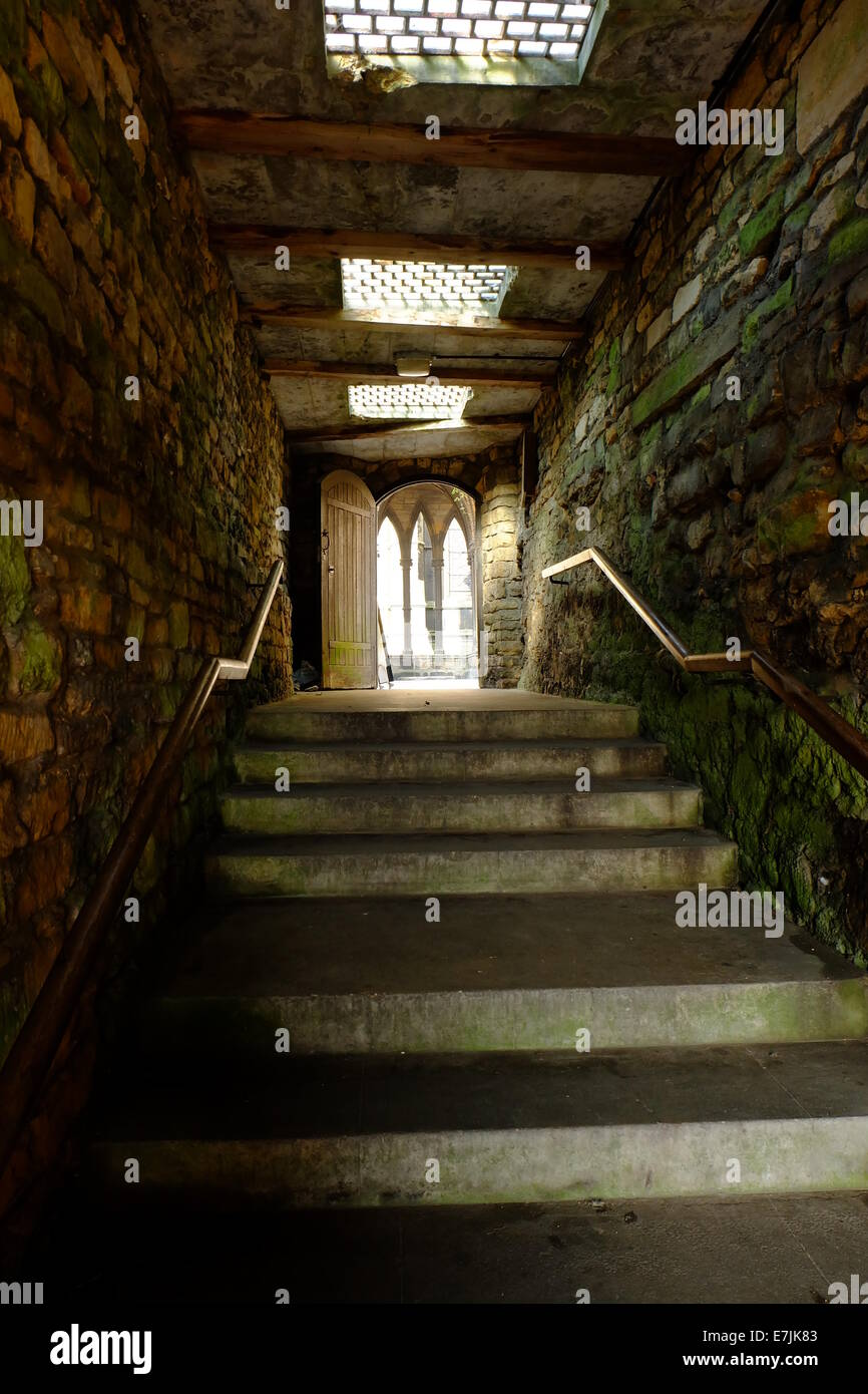 View of stairs looking up to a sun lit door, old damp green stone walls either side, streams of light from sky lights. - Stock Image