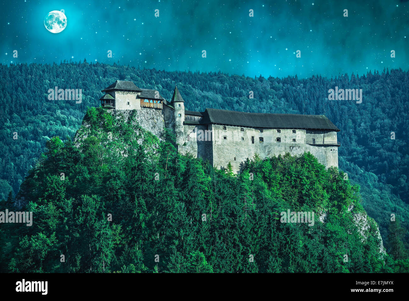 Scary castle in a forest at night with moon Stock Photo