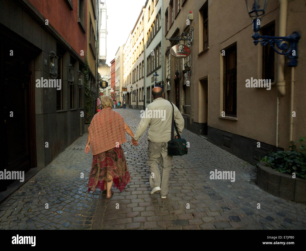 Older couple walking through the old streets of the historic city center of Cologne, Germany - Stock Image