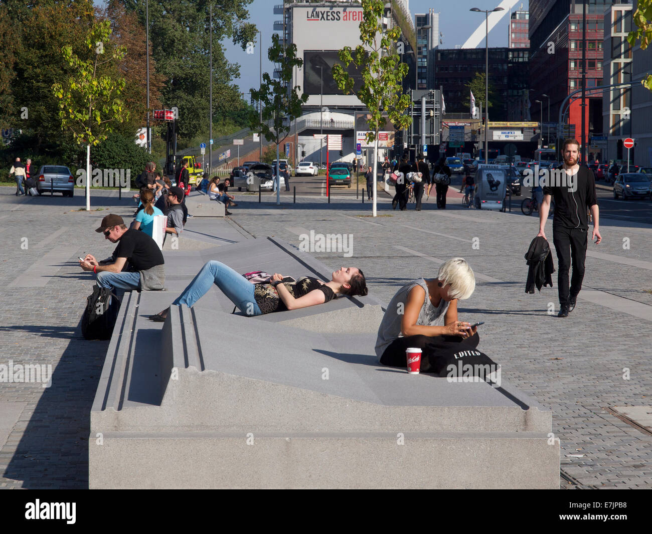 Concrete street furniture with young people relaxing in the sun and using mobile phones at Cologne train station, - Stock Image