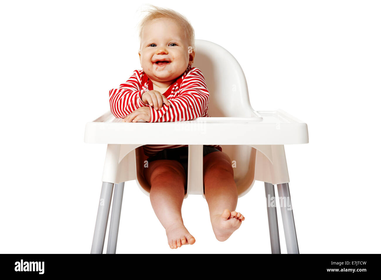 Portrait of baby with dirty mouth after eating. Baby sitting on chair. - Stock Image