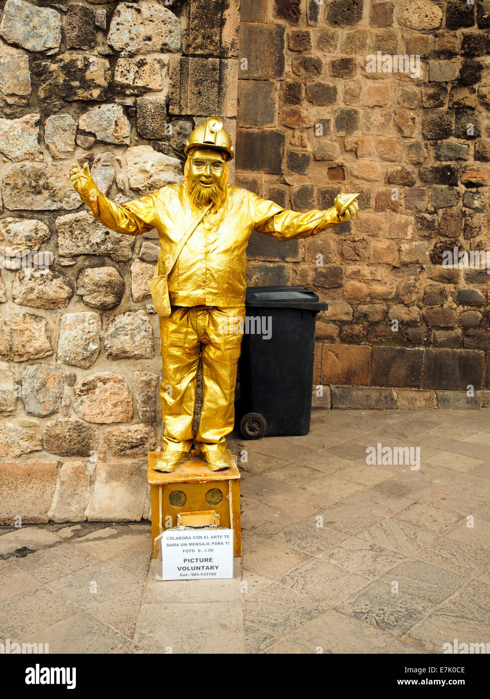Human statue street performer in golden clothes - Cusco, Peru - Stock Image